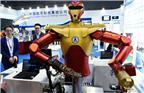 """2015年11月3日,上海,在上海开幕的2015中国国际工业博览会,中国航天首次展出机器人航天员。参观者在观看外形酷似""""钢铁侠""""的机器人航天员。 主要用来辅助或替代航天员开展在轨操作,未来可应用于空间站、载人登月等有人环境,辅助航天员扩大活动空间和工作空间,降低航天员出舱风险。"""