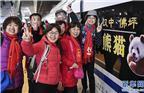 12月6日,旅客在西安北站首发的熊猫号动车前留影。当日,西安至成都高速铁路全线开通运营。全线开通初期将安排动车组列车19对,成都至西安的最短旅行时间压缩至4小时7分。年底实施新的列车运行图后,两地间最短旅行时间将压缩至3小时27分,较原来缩短约7小时。新华社记者陶明摄