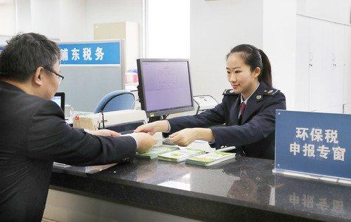 图为4月1 日上午,巴斯夫新材料有限公司财务人员从上海浦东新区税务局工作人员手中,接过上海市开出的首张环境保护税税票。这也是全国首张环境保护税税票。新华社记者方�瓷�