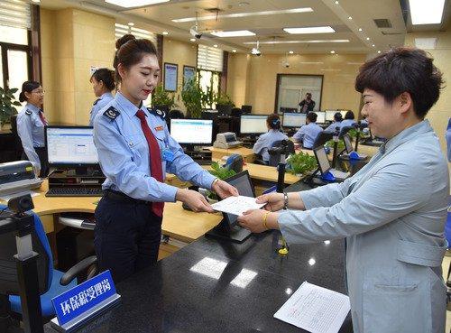 图为4月2日,兰州地税局工作人员向西北永新涂料有限公司发出甘肃省首张环保税税票。新华社发 张睿摄