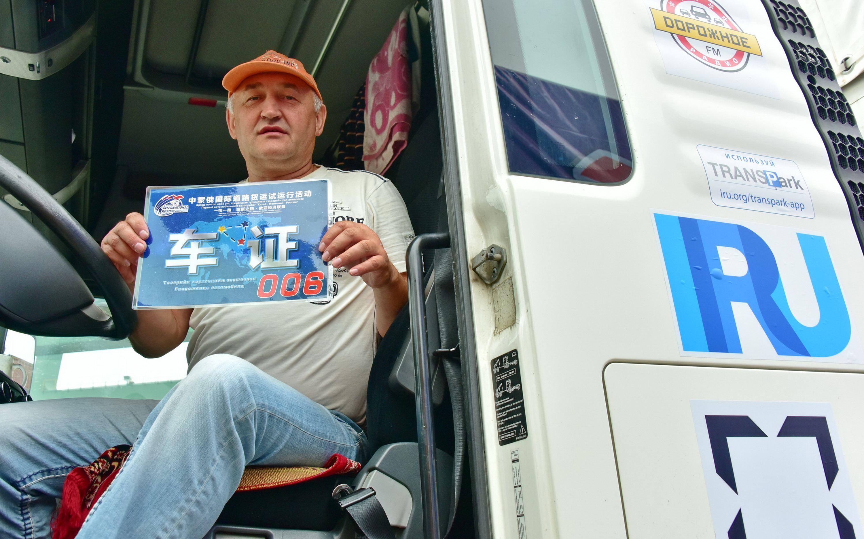 2016年8月18日,參加中蒙俄國際道路貨運試運行活動的俄方司機向第一財經記者展示活動車證。攝影/章軻