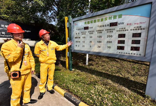 廣州華潤熱電有限公司總經理韋丹(左2)向記者介紹燃煤機組的實時排放情況。攝影/章軻