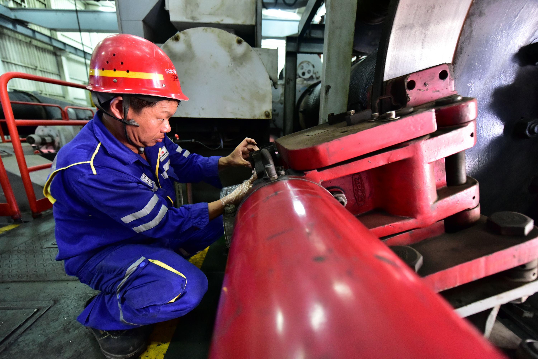 羅健在港口集裝箱裝卸橋內部調試設備。攝影/章軻