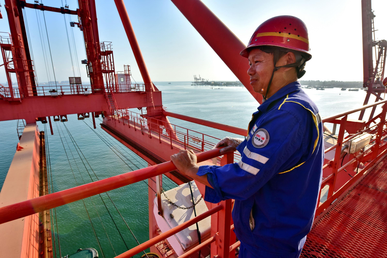 羅健站在60多米高的港口集裝箱裝卸橋上遠眺。攝影/章軻