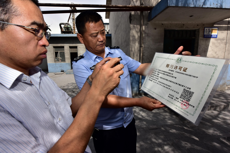 執法人員在拍攝寧夏諾力環保新材料有限公司《排汙許可證》。攝影/章軻