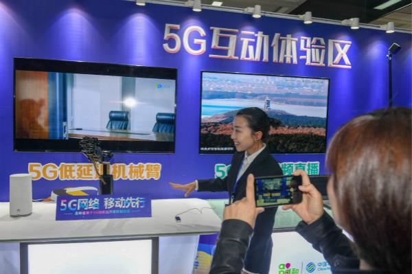 3月28日,在长春地铁2号线文化广场站5G互动体验区,工作人员与连接5G网络的机械臂进行互动。