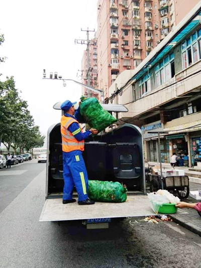 長寧區華陽街道的保潔人員上門接收餐飲垃圾。