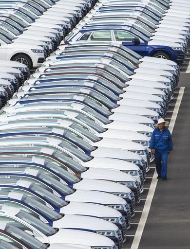 在位于吉林長春的一汽-大眾倉儲停車場內,職工對停放在此的汽車進行巡檢(7月9日攝)。新華社