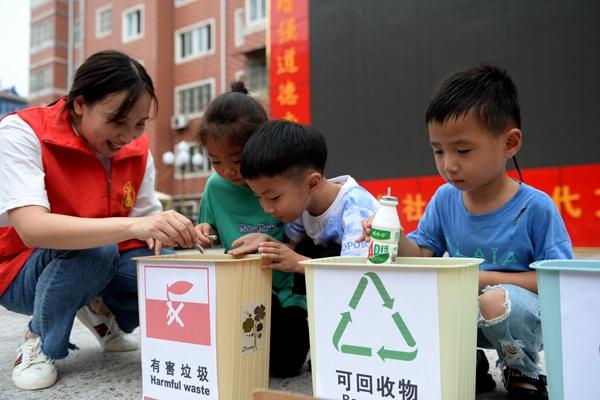 近日在安徽,志愿者在指导小朋友进行垃圾分类。本文图片除署名外均来自新华社