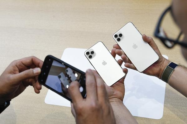 發布會上,蘋果手機壓軸亮相。圖為人們體驗蘋果手機新品。新華社