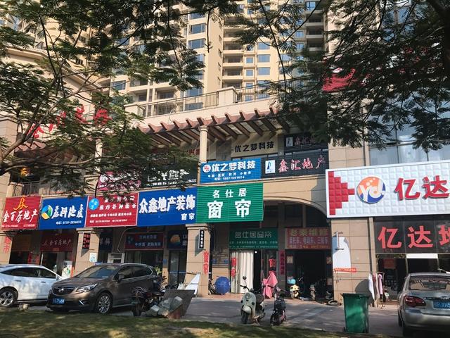 北部湾大道上颇有名气的阳光海岸楼盘,楼盘商业街的左侧房产中介以及装饰建材商铺聚集 吴俊捷摄
