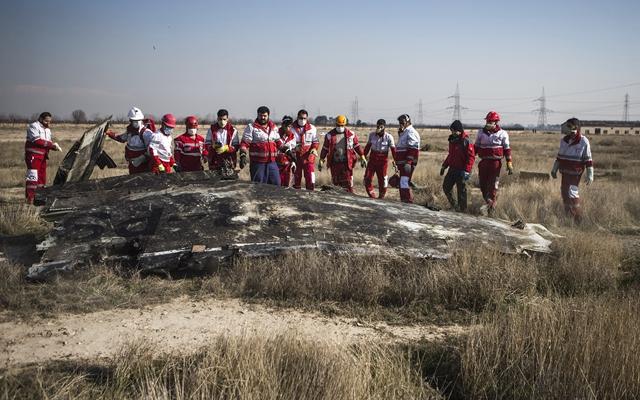 1月8日,在伊朗德黑兰霍梅尼国际机场附近,救援人员在坠机现场工作。