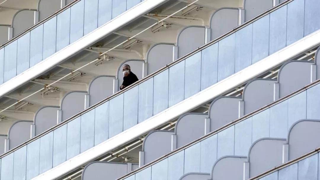 △2 月 6 日,一名被隔离的乘客站在自己房间的阳台上。图片来源 | 美联社