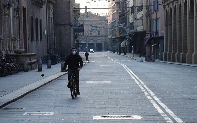 3月21日,在意大利博洛尼亚,一名男子戴着口罩在街道上骑行。新华社