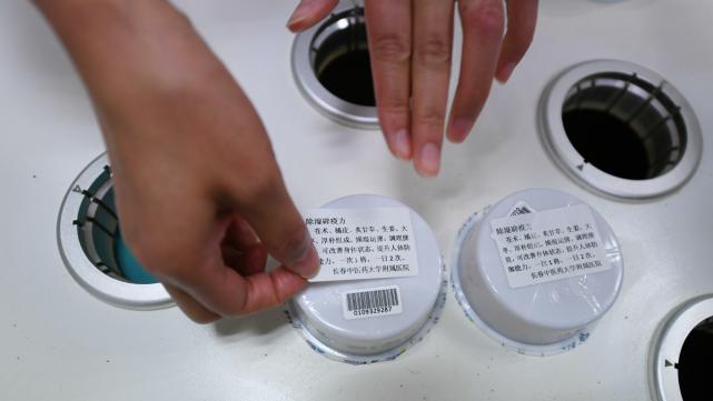 """5月26日,长春中医药大学附属医院药学部工作人员正在调剂""""除湿防疫""""中药配方颗粒。"""