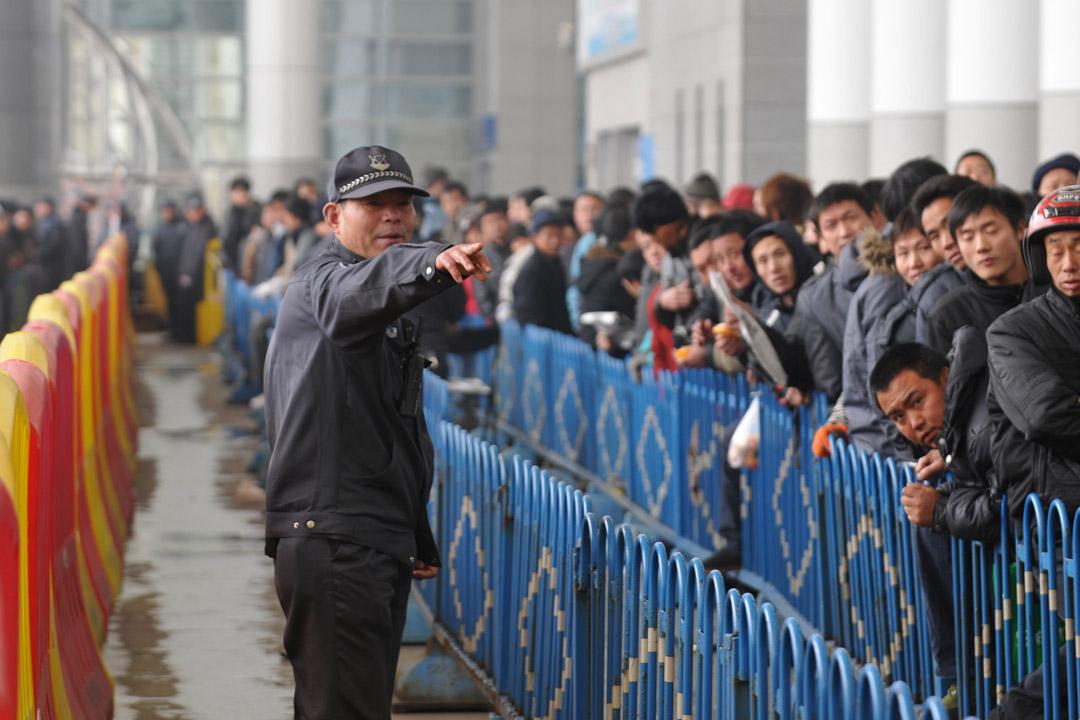 宁波国际会展中心春运铁路临时售票处等候区,保安正在维持排队秩序.