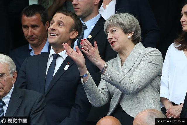"""当地时间2017年6月13日,法国圣丹尼斯,英国女首相特雷莎-梅出访法国,与法国总统马克龙一起观看法国与英格兰的足球友谊赛,两人热聊,心情大好。据报道,""""豪赌""""议会选举失利后,英国首相、保守党党首特雷莎-梅正面临党员讨伐。她寻求与北爱尔兰的民主统一党达成松散同盟协议,但是下台危机仍未消除。"""