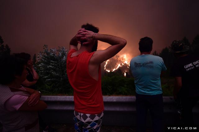 图为当地时间2017年6月18日,葡萄牙Mega Fundeira遭山火袭击,当地居民看着森林里大火蔓延。