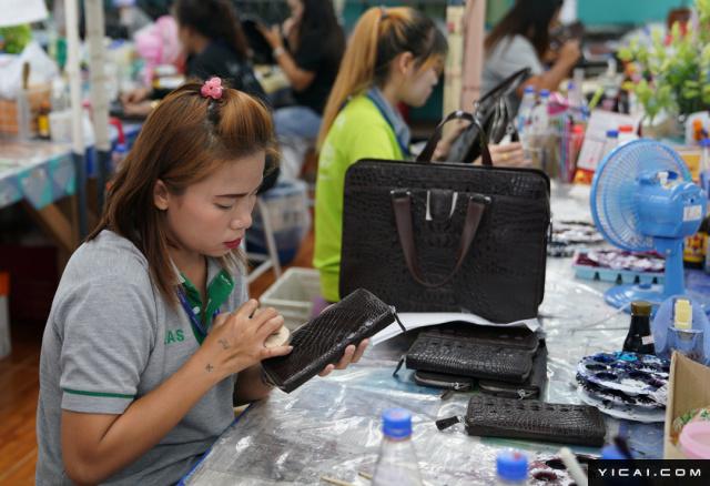 据Rueangnet介绍,鳄鱼皮制品包括Birkin手袋,每个售价可达8万泰铢(约合人民币1.6万元),还有用鳄鱼皮制成的衣服,售价更是高达20万泰铢(约合人民币4万元)。图为工人在制作鳄鱼皮手包。泰国阿育他亚府,一个工人在擦拭一个鳄鱼皮制成的钱包。