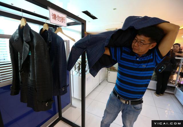 当地时间2017年5月20日,泰国春武里省,是拉差鳄鱼湖里,一名顾客在试穿鳄鱼皮制成的衣服。