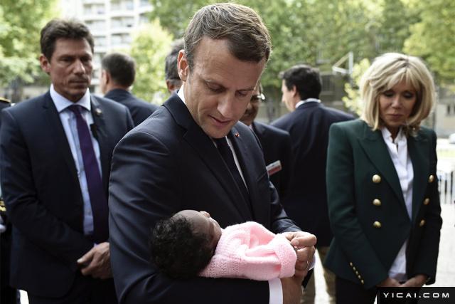 当地时间2017年8月9日,法国巴黎,法国总统马克龙与妻子布丽吉特参观Robert-Debre儿科医院。图为马克龙抱着婴儿秀亲民。