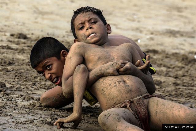 当地时间2017年8月7日,印度孟买,马洛尼附近的Koliwada村庄里,印度传统泥地摔跤正在精彩上演。泥地摔跤(Kushti)是印度的一项古老而传统的活动,通常在一片泥潭或是印度特有的泥地摔跤场举行。现在,这项古老的运动随着现代摔跤的流行渐渐落没,仅有少数人还在坚持着,希望把这一传统运动传承下去。