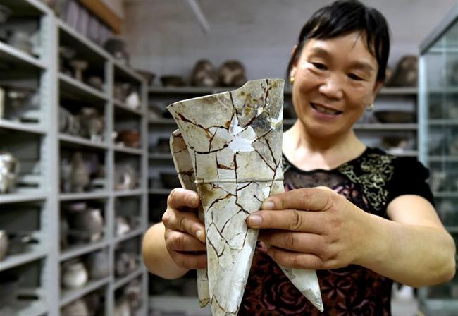 二里头遗址女考古技工王丛苗在洛阳偃师二里头考古队展示一件修复后的文物。新华社发(李嘉南 摄)