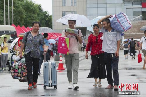 资料图:8月30日,3000余名2018级新生来北京大学报到。图为家长们帮新生拿着行李,冒雨前往学校宿舍。中新社记者 贾天勇 摄