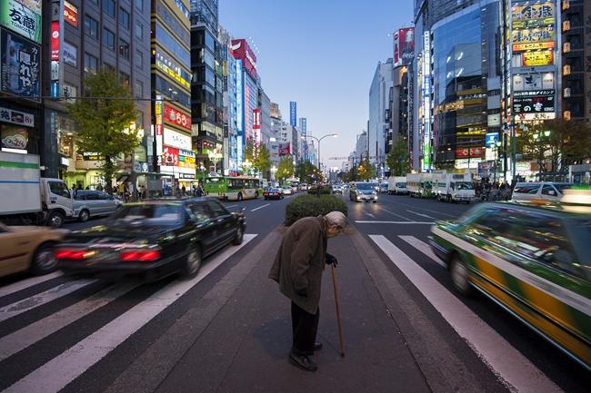 在华灯初上的荣华街头,一位拄着拐杖独自前走的日本老人。图片来自视觉中国