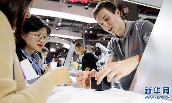 11月5日,库卡公司工作人员(右)向参观者展示机器人手臂模型。 来源:新华社