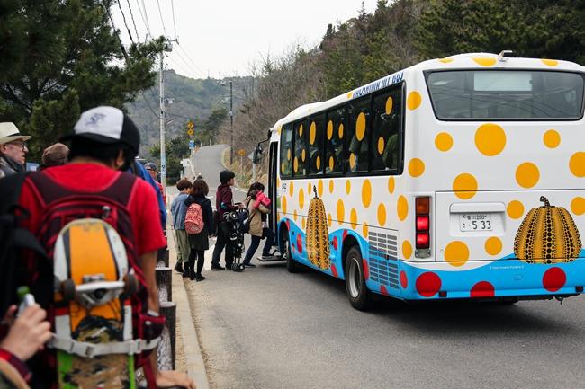 在直岛上,排队乘坐涂满草间弥生标志性波点符号接驳车的游客。何海洋 摄