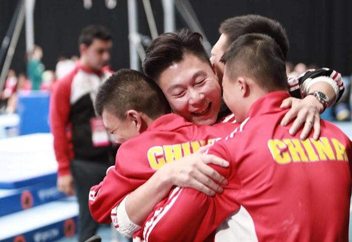 赛场边,李幼鹏与中国特奥体操活动员们拥抱。    摄影/罗四维
