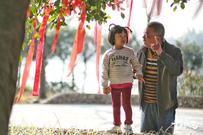 廖志其在鱼咀村的祈愿树下为孩子讲述村里的故事。  摄影/张健