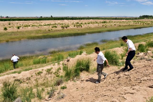 2018年6月27日,中央第二环境保护督察组在内蒙古巴彦淖尔市督察乌梁素海污染整治情况。图为督察人员走下干渠检查。摄影/章轲
