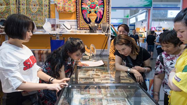 在第5届中国-南亚博览会上,来自印度的客商(左二)向顾客推介特色商品
