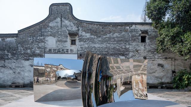"""安尼施·卡普尔的《双眩》是西栅景区""""流量""""最多的展品,每天吸引着游客驻足拍照。两面不锈钢曲面的镜像,容纳江南水乡斑驳墙面和如织游人,倒置、正向的镜面,反射出的虚像向无限深处展开。  供图/乌镇当代艺术邀请展"""