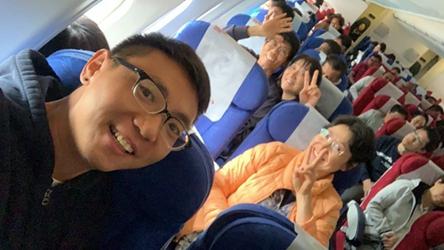 游客在在回程的航班上合影。