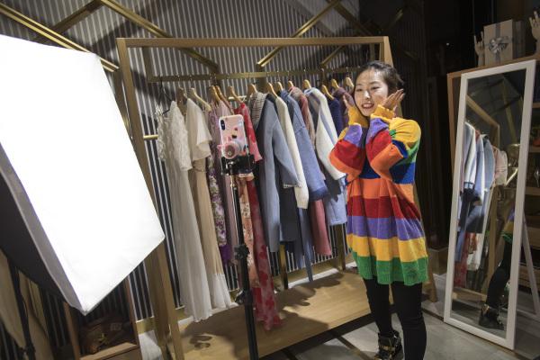 在武汉汉正街的一家网红电商中心,主播通过直播的方式向观众推销服饰。新华社资料图