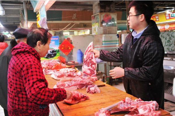 2月15日,在山东青岛一农贸市场,市民在选购猪肉。新华社发