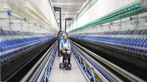 工人在山东邹平市魏桥纺织公司智能化车间对生产线进走巡检。 新华社图