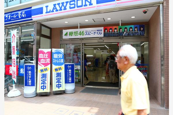 """一名老人从日本东京的""""多功能""""健康便利店前走过。新华社资料图"""
