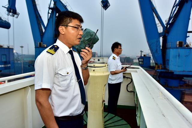 """6月19日傍晚,25万吨级散货船""""山东人和""""轮船长丁茂家在指挥船舶离港。摄影/章轲"""