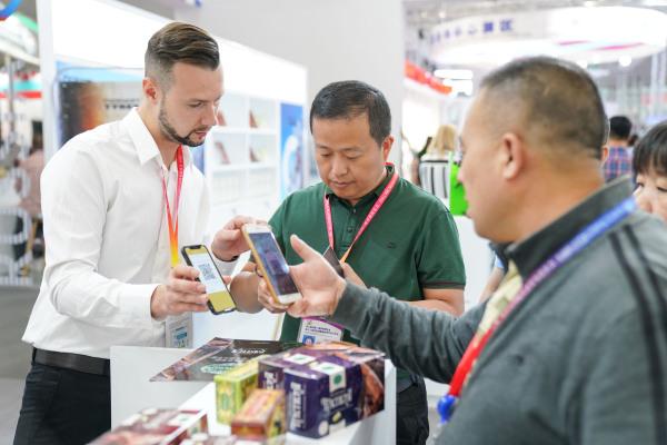 6月15日,在第六届中国-俄罗斯博览会上,参观者购买商品后用微信向俄罗斯参展商(左一)付款。新华社