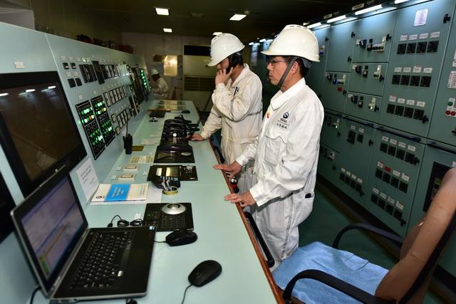 """6月19日晚,""""山东人和""""轮集控室。海员们正在做开航前的试车。摄影/章轲"""
