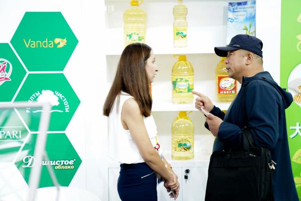 6月15日,参观者(右)在第六届中国-俄罗斯博览会上向一位俄罗斯参展商咨询产品。新华社