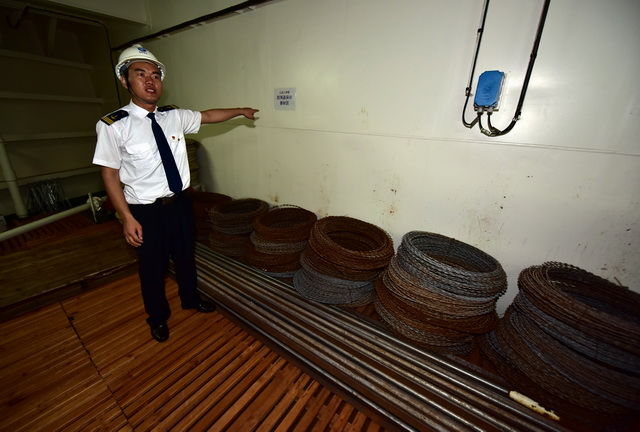 """山东人和""""轮的防海盗设施。图为海员向记者展示防海盗刺钢丝。摄影/章轲"""