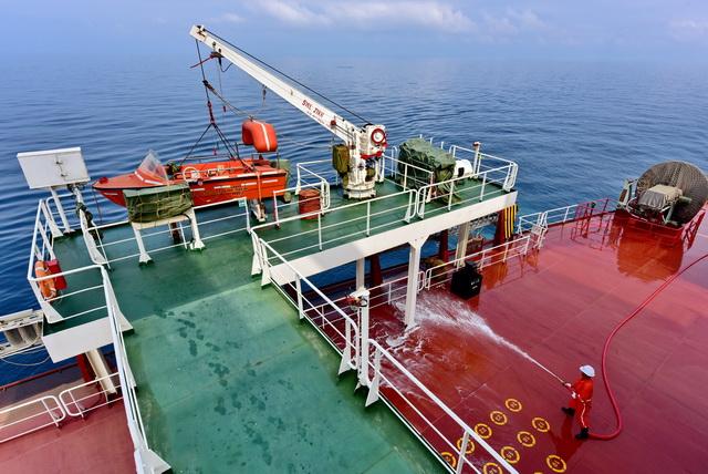 """6月21日上午,山东海运25万吨级散货船""""山东人和""""轮行驶在黄海上。图为船员们正在对甲板进行清洗。摄影/章轲"""