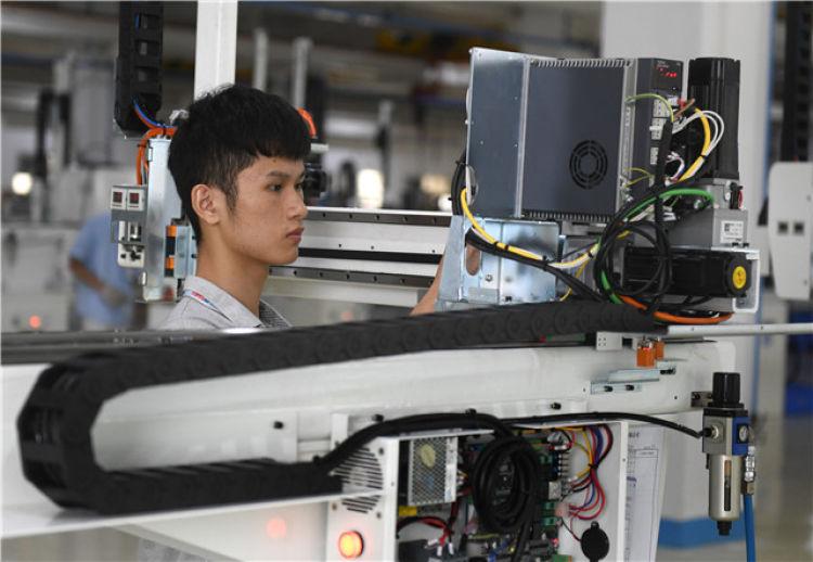 在工业机器人生产企业广东东莞拓斯达科技股份有限公司,工人在生产线上工作(2019年7月11日摄)。新华社记者卢汉欣摄