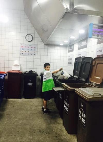 开开大楼的小志愿者在帮忙投放垃圾。
