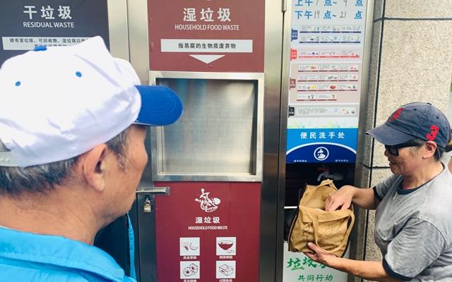75岁的志愿者黄建明(左)在查看浦江新城小区居民干湿垃圾分类情况
